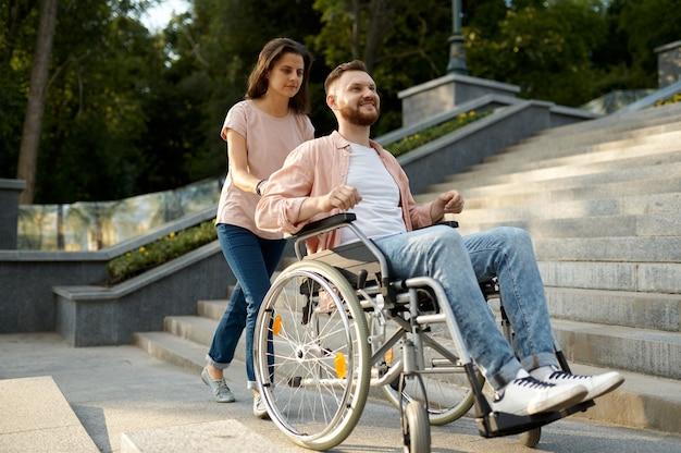 휠체어를 탄 가족 부부가 공원의 계단을 올라갑니다. 마비된 사람과 장애, 장애인을 돌봅니다. 웃는 남편과 아내가 함께 어려움을 극복하고 따뜻한 관계