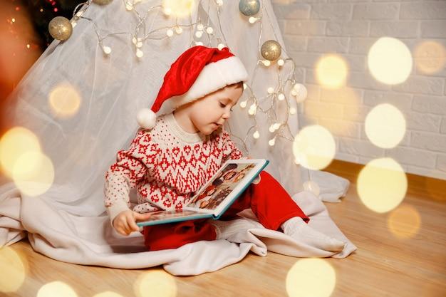 Семейные уютные моменты улыбающегося ребенка, смотрящего на фотоальбом дома