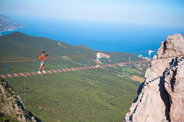 ロープのつり橋の割れ目を横切る家族黒海の背景クリミアロシア
