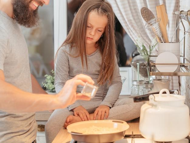 Семейный кулинарный класс. отец учит свою маленькую дочь, как готовить. любопытная девушка внимательно наблюдает.