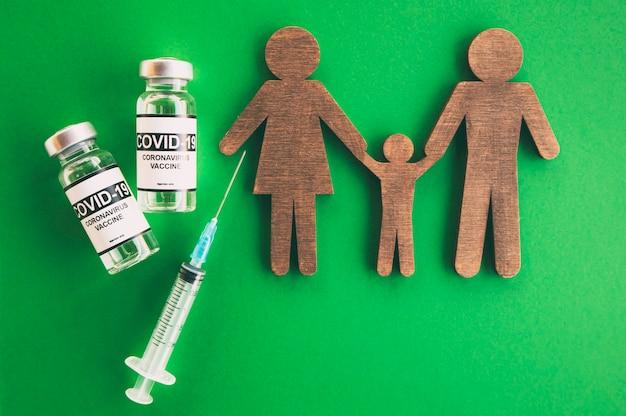 가족이 끊고 코비드 19 백신이 탁자 위에 놓여 있습니다. 가족 예방 접종의 개념입니다. 어린이와 부모를 위한 코로나바이러스 백신