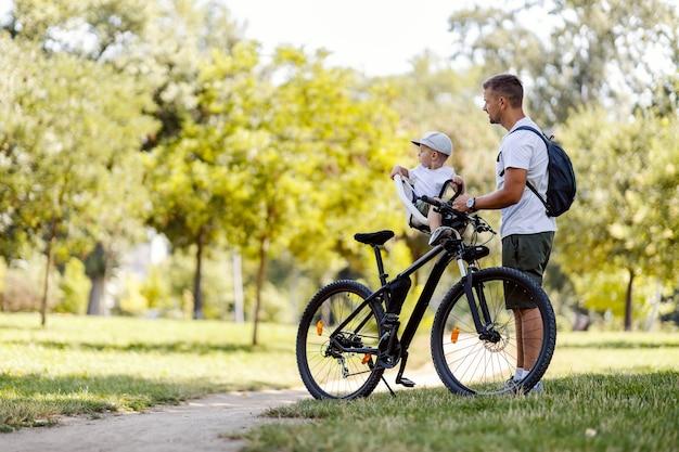 가족 자전거. 화창한 여름날 푸른 공원에서 아버지와 아들이 자전거를 타고 휴식을 취하고 있습니다. 모자를 쓴 유아가 자전거 바구니에 앉아 있고 아빠가 옆에 서 있습니다. 측면보기