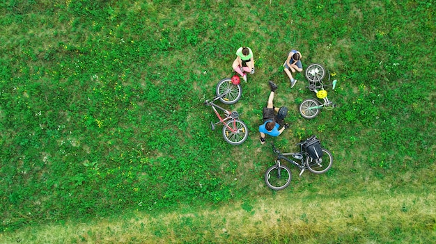 Family cycling on bikes aerial view from above, happy active parents with child have fun and relax on grass, family sport and fitness on weekend