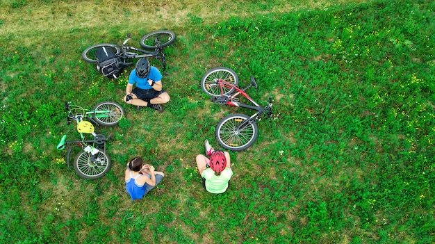 Family cycling on bikes aerial view from above, happy active parents with child have fun