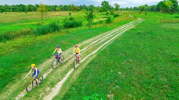 Family cycling on bikes outdoors aerial view from above, happy active mother with children have fun, family sport and fitness