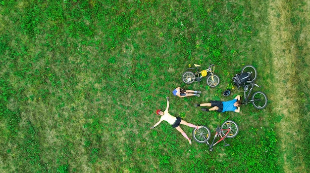 Family cycling on bikes outdoors aerial view from above, happy active parents with child have fun and relax on grass, family sport and fitness on weekend