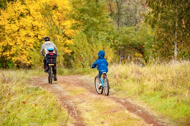 Family cycling in golden autumn park, active father and kids ride bikes, family sport and fitness outdoors