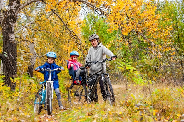 Family cycling in golden autumn park, active father and kids ride bikes, family sport and fitness with children outdoors