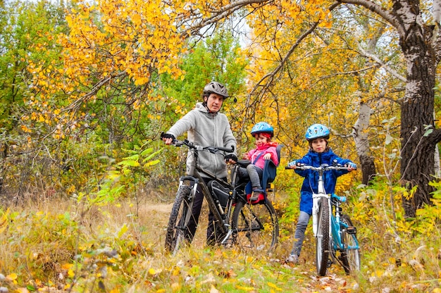 Family cycling in golden autumn park, active father and kids ride bikes, family sport and fitness with children outdoors Premium Photo