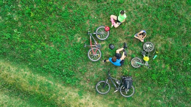 위에서 자전거를 타고 공중에서 자전거를 타는 가족, 자녀가있는 행복한 활동적인 부모는 주말에 잔디, 가족 스포츠 및 피트니스에서 즐거운 시간을 보내고 휴식을 취합니다.