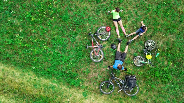위에서 자전거를 타고 공중에서 자전거를 타는 가족, 자녀가있는 행복한 활동적인 부모는 주말에 잔디, 가족 스포츠 및 피트니스에서 재미 있고 휴식을 취합니다.