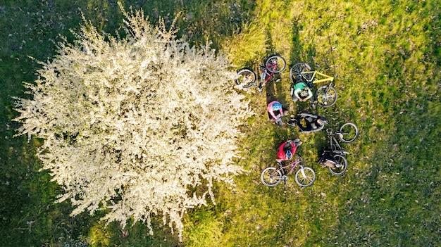 Семья катается на велосипедах весной с высоты птичьего полета сверху счастливые активные родители с детьми