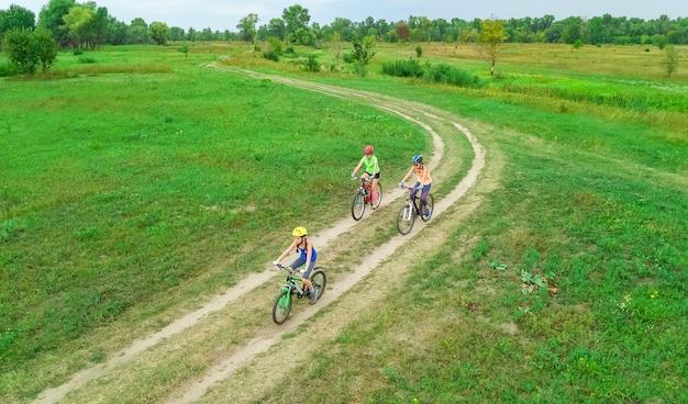 上から自転車屋外空撮でサイクリング家族、子供と幸せなアクティブな母親が楽しい、家族のスポーツとフィットネス