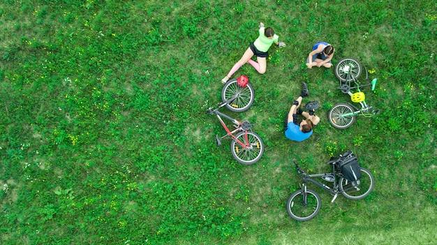 家族で上から自転車屋外空中サイクリング、子供と幸せなアクティブな親が楽しい時を過し、週末に草、家族のスポーツ、フィットネスでリラックス