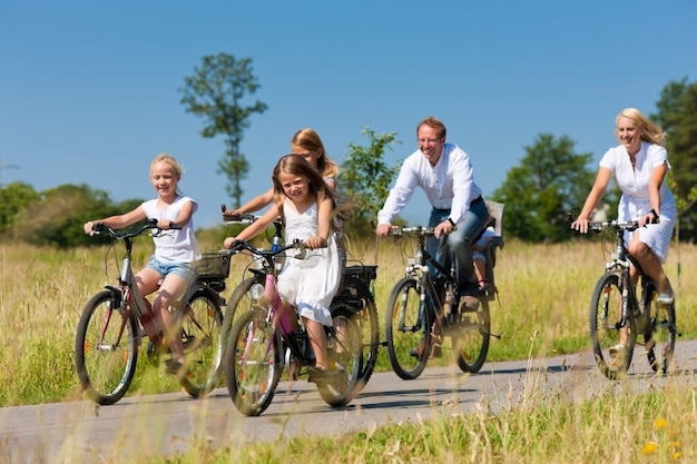 Family cycling outdoors in summer