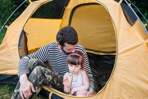 テントで休んでいる家族のお父さんと娘