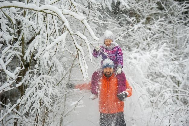 家族のお父さんと娘は冬に雪に覆われた森の中を歩きます