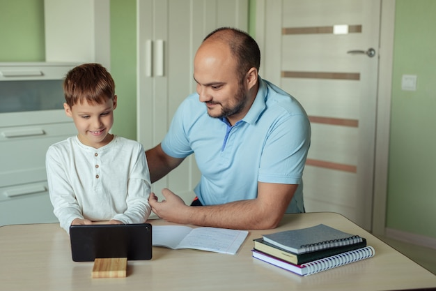 家族のお父さんと息子は自宅の部屋のテーブルに座って、タブレットを使用して宿題をしています。