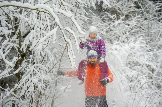Family dad and daughter walk in the snow-covered forest in winter