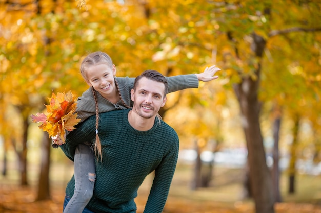 Family of dad and kid on beautiful autumn day in the park