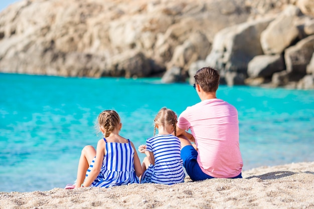 Family of dad and kids on white sandy beach in european seashore