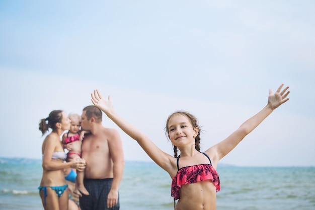 바다 배경의 아름답고 행복한 해변에서 가족 아빠, 엄마, 소녀, 아기