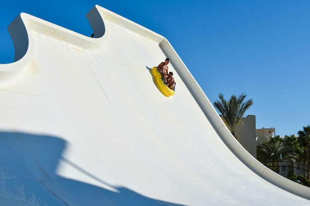 A family of dad and son ride a tubing on a fast water attraction in an aquapark