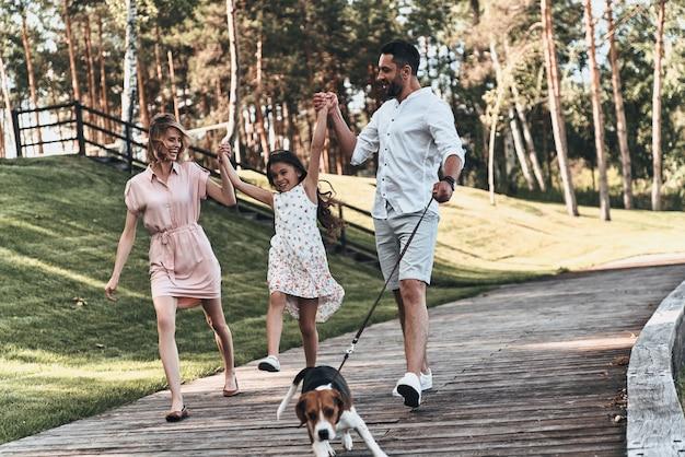 가족의 날. 3명의 젊은 가족이 손을 잡고 함께 공원을 걷는 동안 웃고 있습니다.