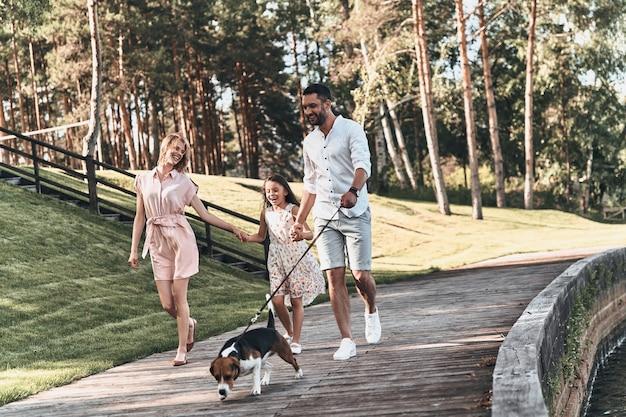 가족의 날. 공원에서 산책하는 동안 손을 잡고 웃고 있는 3명의 젊은 가족의 전체 길이