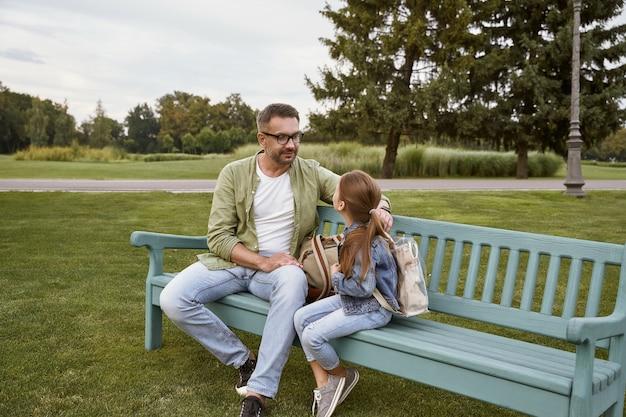 자연 속에서 가족의 날 젊은 아버지와 공원의 나무 벤치에 앉아 있는 귀여운 딸