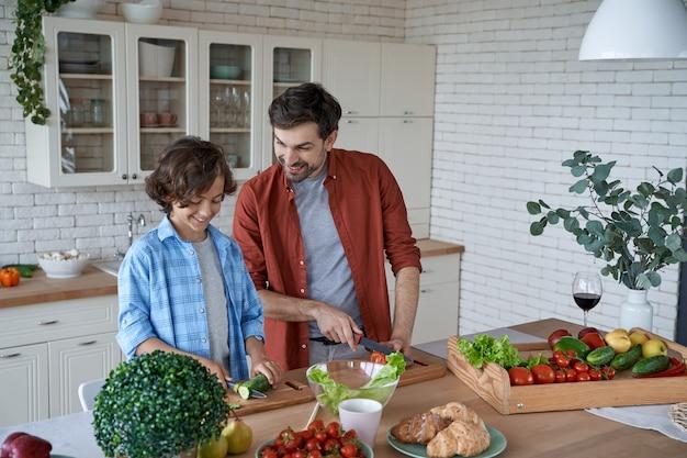 家族の日若い父と息子が立っている間に新鮮な野菜を切るサラダを準備します