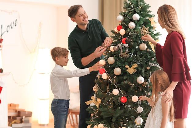 部屋の美しいクリスマスツリーを飾る家族
