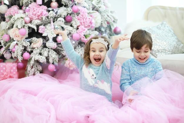 Семья украшает красивую живую елку. любящая семья с подарками в комнате. счастливая семья в отпуске.