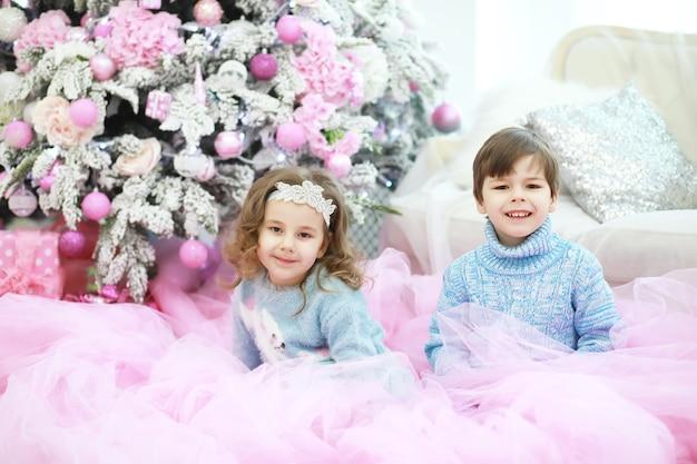 아름다운 라이브 크리스마스 트리를 장식하는 가족. 방에 선물을 들고 사랑하는 가족. 휴일에 행복한 가족.