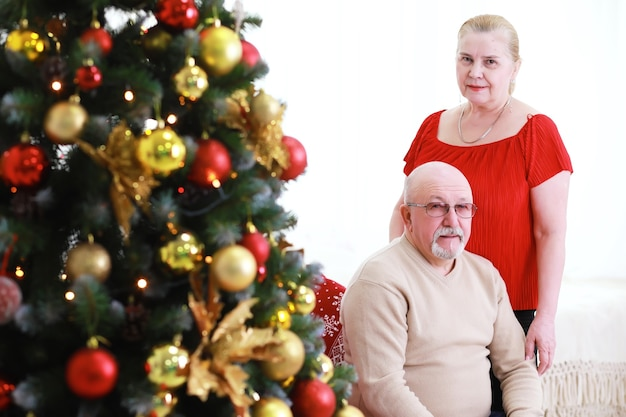 Семья украшает красивую живую елку любящая семья с подарками в комнате