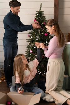 Family decorating the christmas tree together