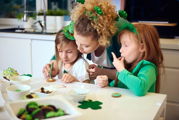 Family decorating cookies at kitchen