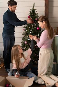 一緒にクリスマスツリーを飾る家族