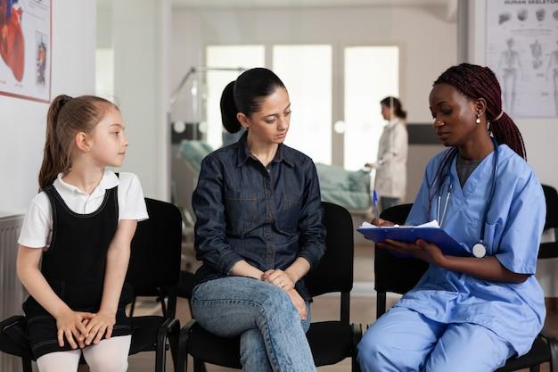 病院でアフリカ系アメリカ人の看護師と治療について話し合う家族