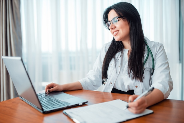 Family doctor concept, specialist sits at laptop