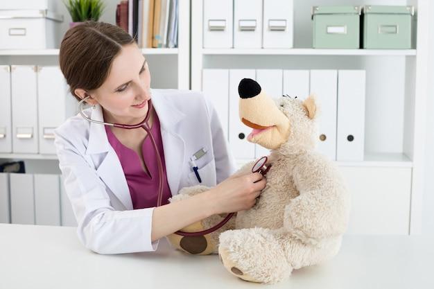 Осмотр семейного врача. красивая улыбающаяся женщина-врач в белом халате исследует плюшевого мишку со стетоскопом, чтобы успокоить и заинтересовать ребенка. играет с маленьким пациентом. медицинская концепция педиатрии