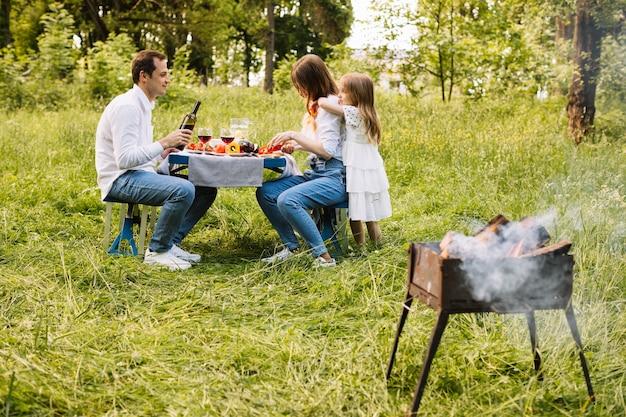Семья делает барбекю на природе