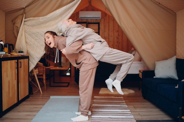 Family doing exercises sports indoors young and senior elderly woman relaxing at glamping camping te...