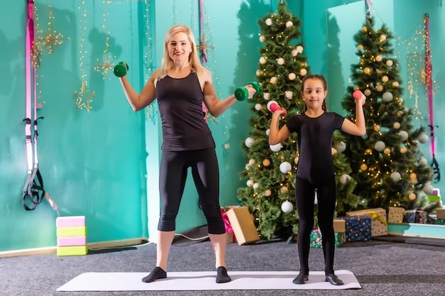 クリスマスツリーの近くでフィットネスをしている家族