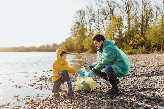 自主的な仕事をしている家族、公園でゴミを拾う