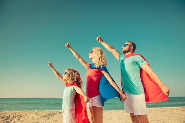 Семья, одетая как супергерой, поднимает руки вверх на пляже