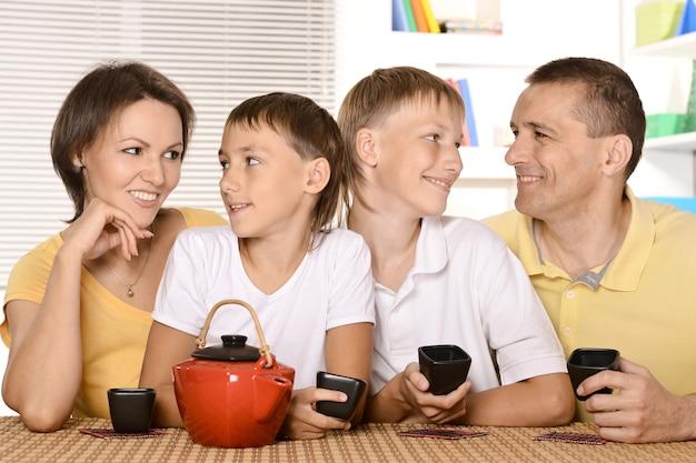 家族が台所のテーブルでお茶を飲む