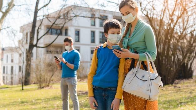 携帯電話でニュースをチェックするコロナ危機の家族