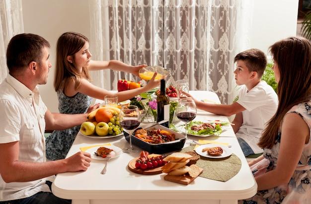 Семья ест за обеденным столом вместе