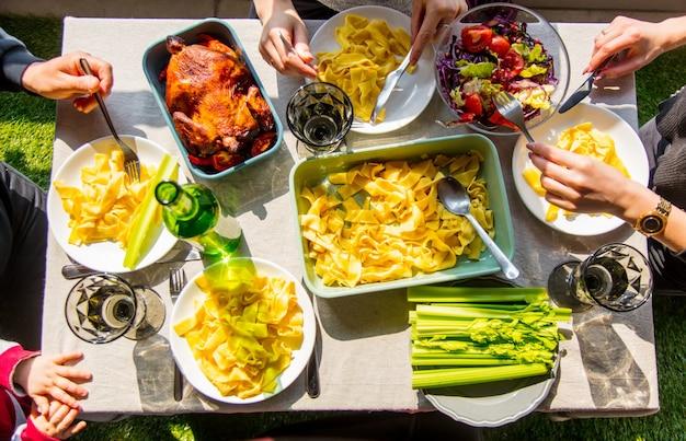 저녁 식사에 닭고기와 스파게티를 먹는 가족. 보기 위